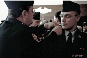 Tom attaching Tommy's Infantry cord after he graduatedBasic Training at Ft Benning, GA.